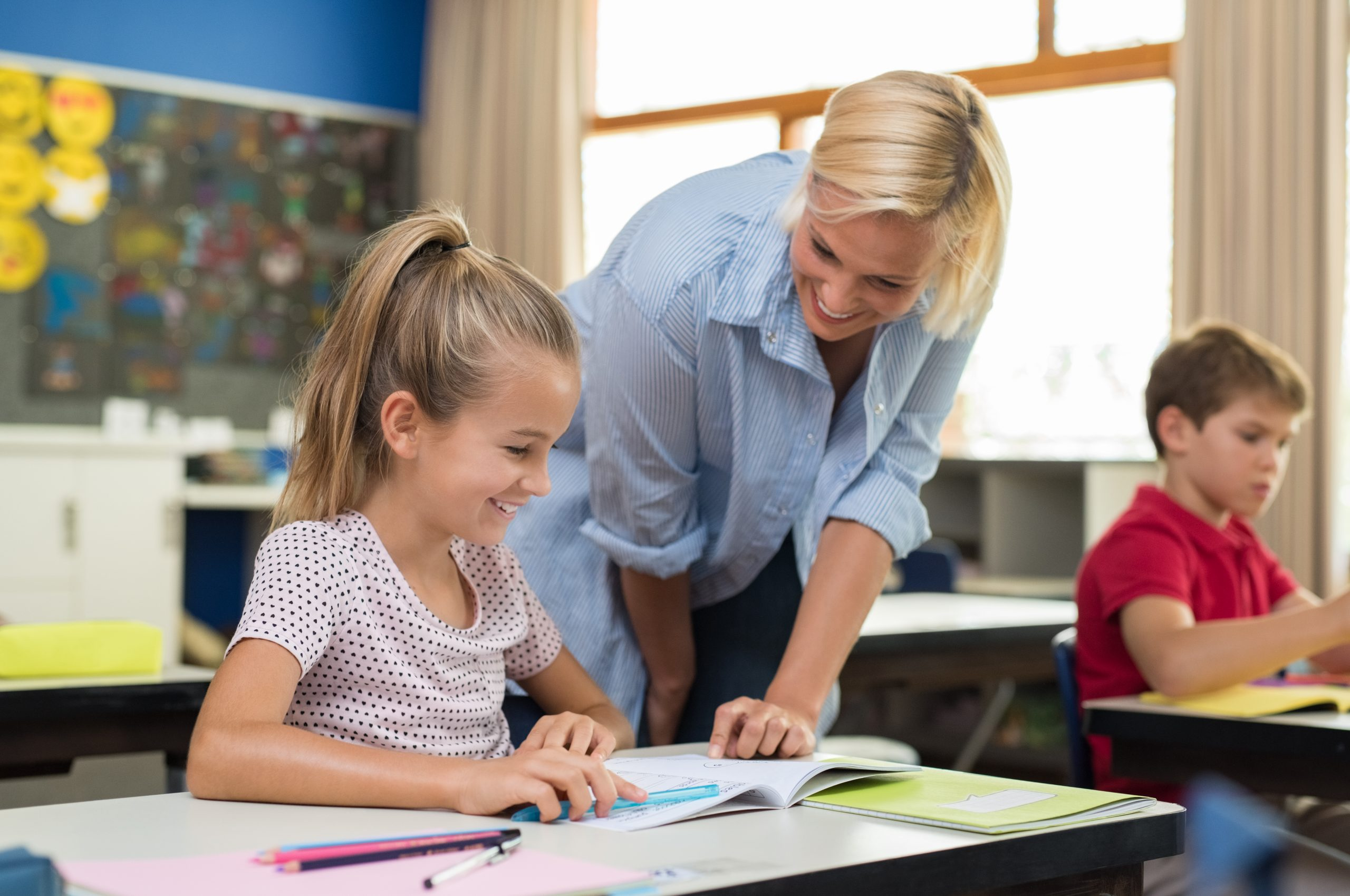Happy teacher helping young girl with study in classroom. Teacher teaching to smiling schoolgirl at elementary school. Diligent child sitting at school desk with tutor.